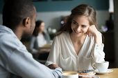 Happy Interracial Couple Flirting Talking Sitting At Cafe Table, African Man Holding Hand Of Smiling poster