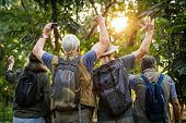 Group of senior adults trekking in the forest poster