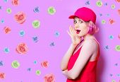 Portrait Of Beautiful Surprised Young Woman In Cap With Roses On The Wonderful Purple Studio Backgro poster