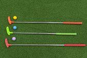 Three Horizontal Mini Golf Putters With Three Mini Golf Balls On Artificial Grass poster