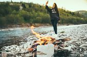 Camping. Young Woman Taking Selfie While Resting On Riverside With Camp Fire poster