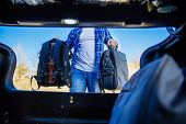 View From Inside Of Trunk. Young Adult Man Putting Bag In Car Trunk. Car Travel Concept poster