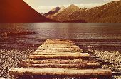 Old Wooden Pier On The Lake. Long Exposure. Landscape View With Wood Bridge In Lake And Mountain Bac poster