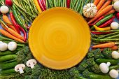 Vegetables Background With Empty Yellow Plate In The Middle. Carrots, Tomatoes, Asparagus, Broccoli, poster