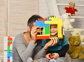 Dad And Kid With Toys On Wooden Background Hold House Wall Made Of Plastic Blocks. Father And Son Wi poster