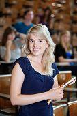 Retrato de joven en el Auditorio de pie con compañeros de clase en segundo plano