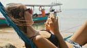 Close-up Of Young Happy Woman In Beachwear Lying On Hammock At The Sandy Beach And Using Smart Phone poster