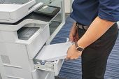Close Up Businessman In Dark Blue Shirt Insert A4 Paper Sheet Into Office Printer Tray poster