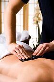 pic of stone-therapy  - woman getting a hot stone massage at a day spa - JPG