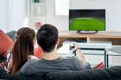 Rear View Of Asian Couple Watching Football At Television In Living Room. Football Festival Concept. poster
