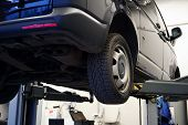 A Commercial Vehicle (minivan) At A Service Station Is Lifted On A Lift For Repair, Tire Fitting. Ca poster