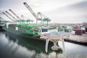 Unmanned Aircraft System Quadcopter Drone In The Air Near Large Shipping Vessel and Dock with Crates poster