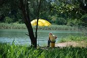 stock photo of fisherwomen  - An elderly fisherwoman sits alone under the shady trees by the side of a northern Italian river - JPG