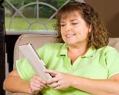 Woman reading book using an e-reader while relaxing at home