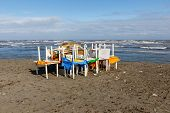 Plastic Tables And Chairs Stacked On The Sandy Seashore Before The Storm, Storm Protection poster