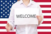 Welcome To Usa, Population Migration. World. A Man Holding Out His Hand On The Background Of The Usa poster