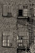 picture of forlorn  - Wall of forlorn building with broken glass windows black and white - JPG