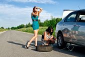 Two Girls Are Fixing A Changing A Tire.
