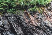 Multilayered Dark Rocky Geological Layers On The Bank Of A Mountain River. Rock With Visible Geologi poster