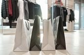 Row of black and white paperbags standing on the floor of boutique on background of new collection o poster
