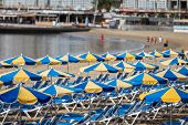 Rows Of Blue Sunbeds With Blue And Yellow Parasols At The Beach Playa De Puerto Rico On The Canary I poster
