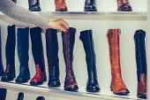 Woman Choosing New Pair Of A Winter Boots At The Store poster