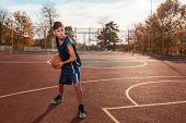 Sports And Basketball. A Young Teenager In A Blue Tracksuit Poses With A Basketball In His Hands And poster