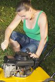 Cute girl repairing lawn mower