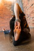 A Close Up View On The Bare Foot Of A Flexible Woman Practicing Advanced Yoga Stretches, Sitting On  poster