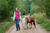 Teenage Girl Walking With A Pony Colt On A Leash Along A Country Road poster