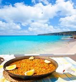 Paella mediterranean rice food by the Balearic Formentera island beach [ photo-illustration]
