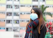 Woman wearing medical face mask in crowded city