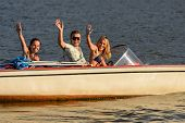 Young people waving from motorboat enjoying summer break