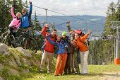 Cheering hikers with raised arms at peak of the mountain