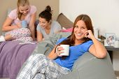Teenager girls reading and drinking at slumber party