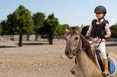 Horseback riding, lovely equestrian - little girl is riding a horse