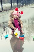 little girl plays with paper ships in a spring puddle