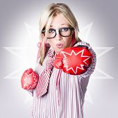 stock photo of starburst  - Tough business woman packing a punch of strength and power wearing boxing gloves on starburst background - JPG