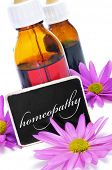 some dropper bottles and a blackboard with the word homeopathy written on it and pink flowers
