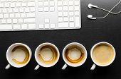 working hours. empty and full cups of fresh espresso with keyboard and headphones, view from above