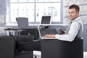 Young businessman sitting in office, resting legs in armchair, using laptop, smiling at camera.
