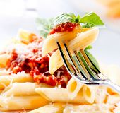 Pasta. Penne Pasta with Bolognese Sauce, Parmesan Cheese and Basil on a Fork. Italian Cuisine. Mediterranean food
