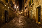 Narrow Alley With Old Buildings In Medieval Town Of Siena, Tuscany, Italy