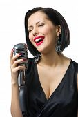 Portrait of female musician with closed eyes wearing black evening dress and keeping microphone, isolated on white. Concept of music and retro fashion