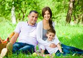 Happy family of three has picnic in green park. Concept of happy family relations and carefree leisu