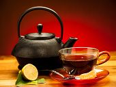 A Cup Of Black Tea With Teapot In The Background