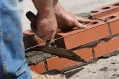 foto of bricklayer  - Bricklayer with trowel setting bricks to a plumb line - JPG