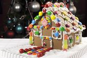 stock photo of gingerbread house  - Beautiful Christmas table setting in front of Christmas Tree featuring a gingerbread house made with frosting and candy sweets - JPG