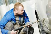 auto repair man worker flatten and align metal body car with hammer in automotive industry