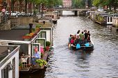 AMSTERDAM - JULY 15: Boat with tourists passing by houseboats on city canal. Houseboats are high dem
